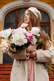 Vista frontal de uma linda mulher segurando um buquê de flores