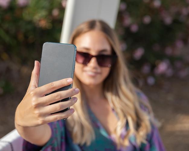 Vista frontal de uma linda mulher tirando uma selfie