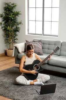 Vista frontal de uma linda mulher tocando violão