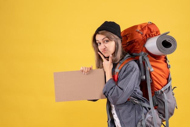 Vista frontal de uma linda mulher viajante com uma mochila vermelha segurando um papelão