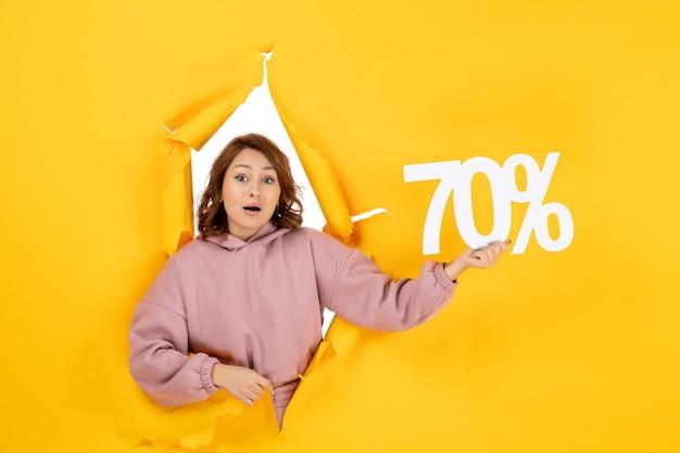 Vista frontal de uma linda senhora confusa mostrando o sinal de porcentagem de setenta em rasgado amarelo