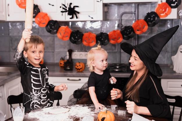 Vista frontal de uma mãe e seus filhos fazendo biscoitos de halloween
