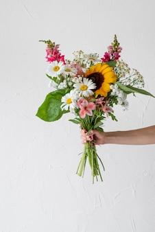 Vista frontal de uma mão feminina segurando um buquê de flores