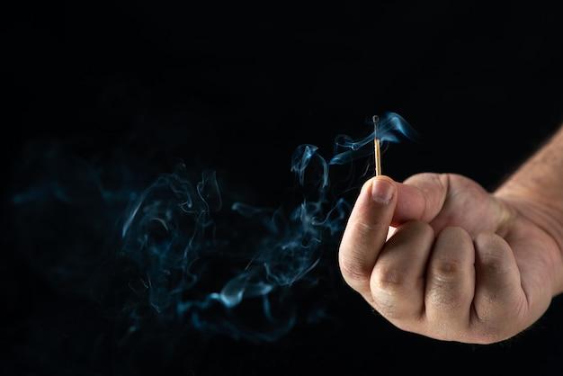 Vista frontal de uma mão masculina segurando fósforos no preto