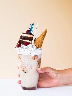 Vista frontal de uma mão segurando um delicioso milk-shake