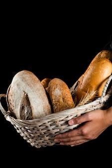 Vista frontal de uma mão segurando uma cesta de pão