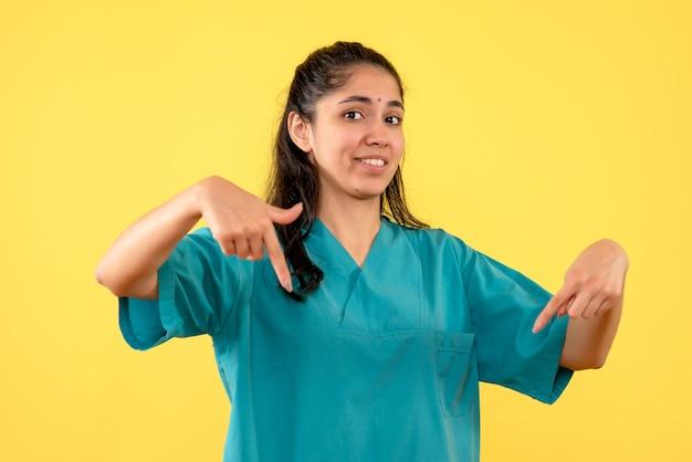 Vista frontal de uma médica bonita apontando para baixo na parede amarela