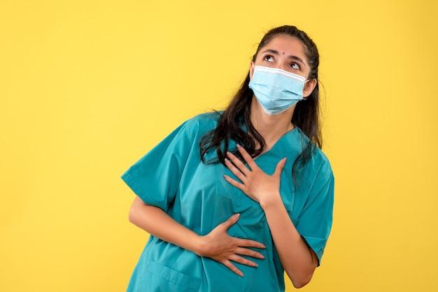 Vista frontal de uma médica bonita com máscara médica, olhando para cima na parede amarela