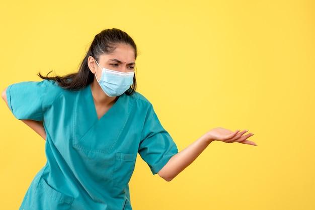 Vista frontal de uma médica bonita com máscara médica segurando-a na parede amarela