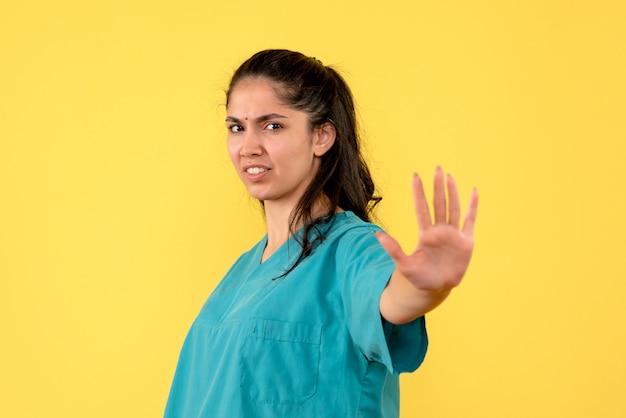 Vista frontal de uma médica bonita fazendo sinal de pare na parede amarela
