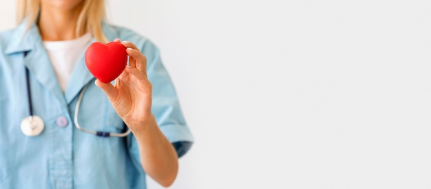 Vista frontal de uma médica com estetoscópio segurando um formato de coração com espaço de cópia