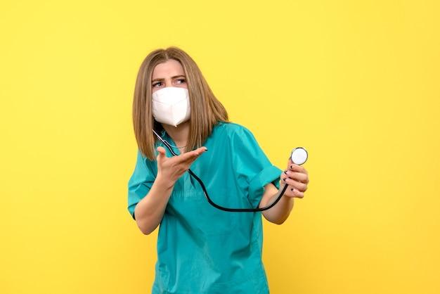 Vista frontal de uma médica com máscara e tonômetro na parede amarela