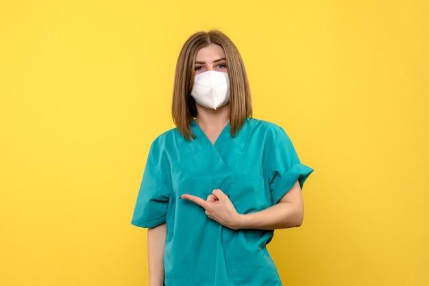 Vista frontal de uma médica com máscara estéril na parede amarela clara