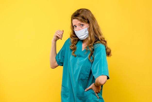 Vista frontal de uma médica com máscara estéril na parede amarela