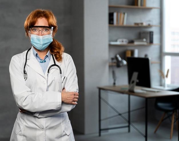 Vista frontal de uma médica com máscara médica e espaço de cópia