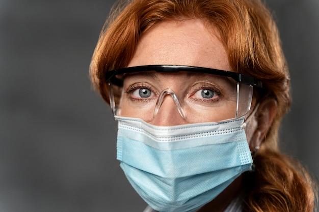 Vista frontal de uma médica com máscara médica e óculos de segurança