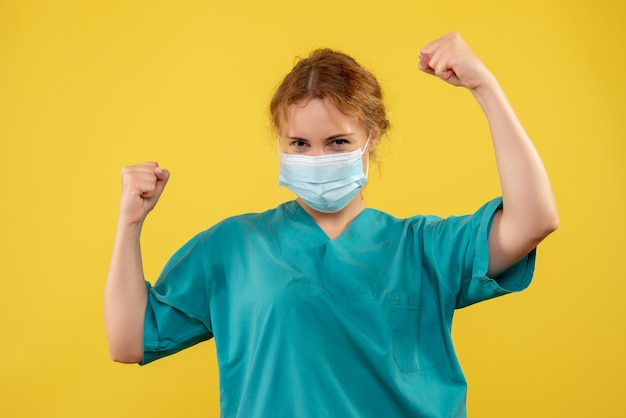 Vista frontal de uma médica em traje médico e máscara regozijando-se na parede amarela