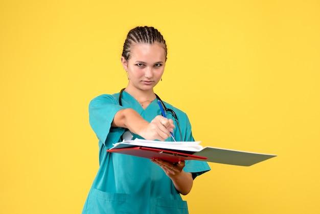 Vista frontal de uma médica em um terno médico com diferentes análises na parede amarela