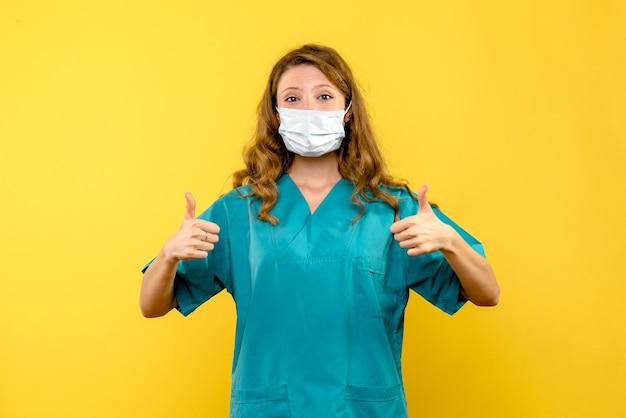 Vista frontal de uma médica posando na parede amarela
