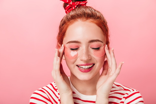 Vista frontal de uma menina caucasiana satisfeita com tapa-olhos. foto de estúdio de uma mulher sorridente em camiseta listrada, fazendo tratamento para a pele.
