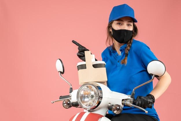Vista frontal de uma mensageira sorridente usando máscara médica preta e luvas, entregando pedidos em fundo cor de pêssego