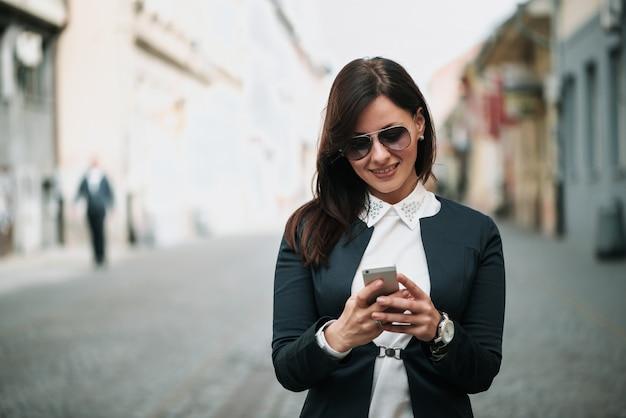 Vista frontal de uma moda mulher feliz andando e usando um telefone inteligente em uma rua da cidade