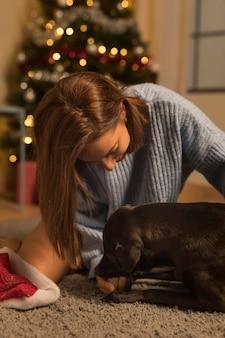 Vista frontal de uma mulher amando seu cachorro no natal