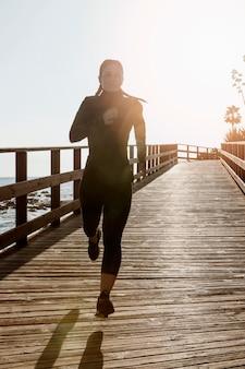 Vista frontal de uma mulher atlética correndo na praia com espaço de cópia