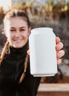 Vista frontal de uma mulher atlética mostrando uma lata de refrigerante