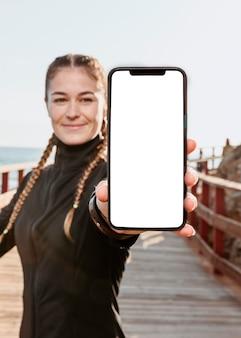 Vista frontal de uma mulher atlética segurando um smartphone