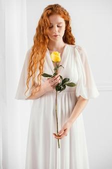 Vista frontal de uma mulher atraente posando com uma flor de primavera