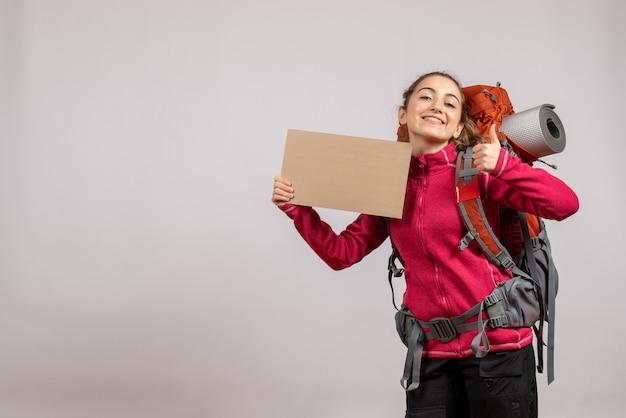 Vista frontal de uma mulher bonita e alegre com uma grande mochila segurando um papelão e dando os polegares para cima