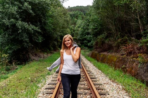 Vista frontal de uma mulher caminhando ao longo de uma via férrea com vegetação