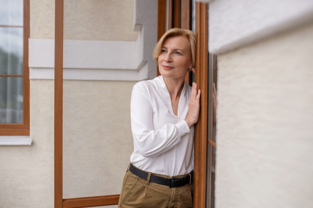 Vista frontal de uma mulher caucasiana madura, calma e pensativa, encostada em uma porta de madeira