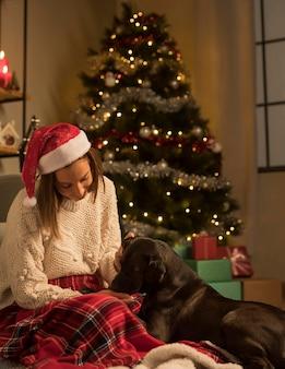 Vista frontal de uma mulher com chapéu de papai noel e seu cachorro no natal
