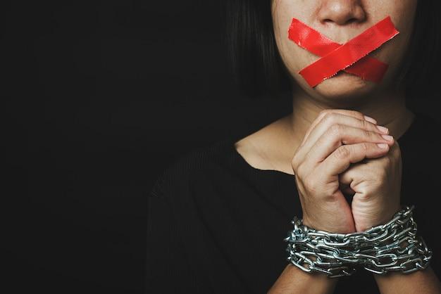 Vista frontal de uma mulher com fita adesiva sobre a boca e as mãos acorrentadas