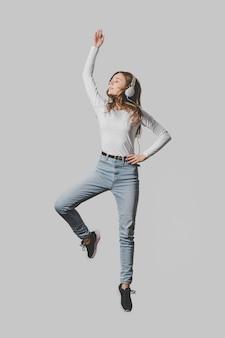 Vista frontal de uma mulher com fones de ouvido pulando no ar
