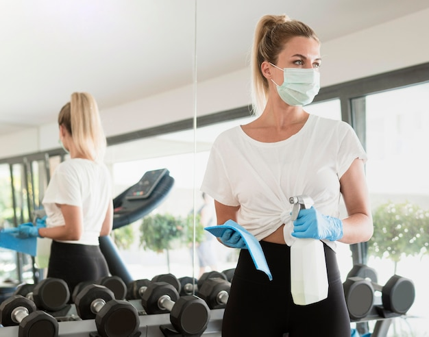Vista frontal de uma mulher com luvas e máscara médica desinfetando pesos na academia
