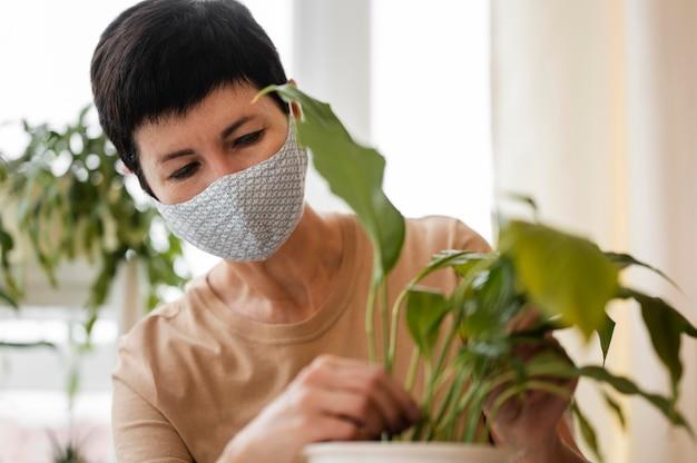 Vista frontal de uma mulher com máscara facial cultivando solo para plantas de interior