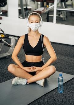 Vista frontal de uma mulher com máscara médica e fones de ouvido, malhando na academia