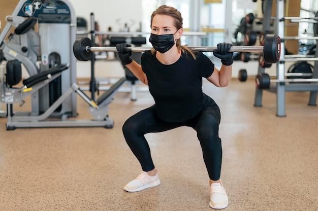 Vista frontal de uma mulher com máscara médica e luvas, fazendo exercícios na academia
