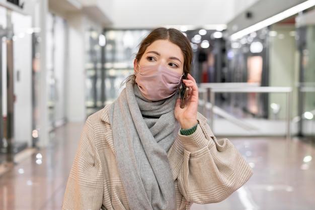 Vista frontal de uma mulher com máscara médica falando ao telefone