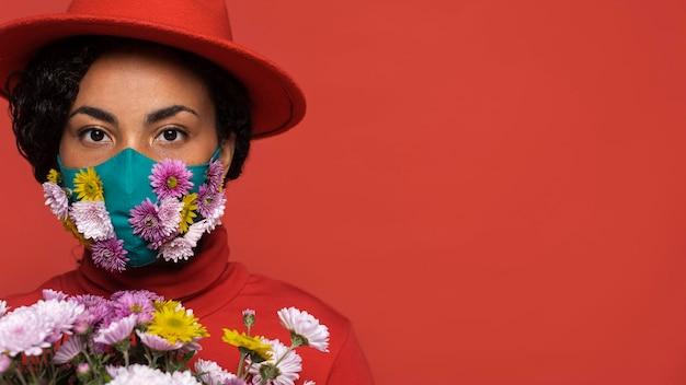 Vista frontal de uma mulher com máscara segurando um buquê de flores