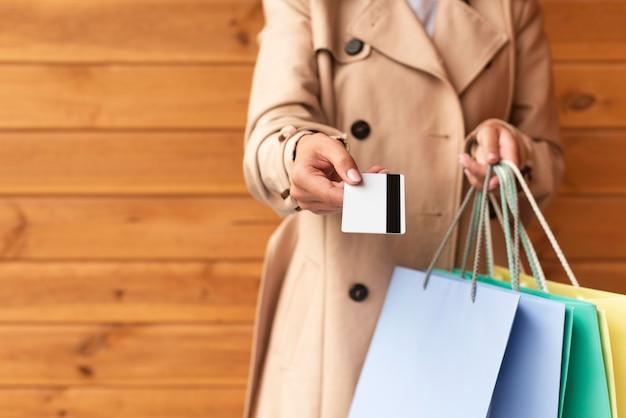 Vista frontal de uma mulher com muitas sacolas de compras oferecendo seu cartão de crédito