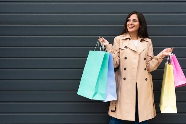Vista frontal de uma mulher com óculos segurando muitas sacolas de compras com espaço de cópia
