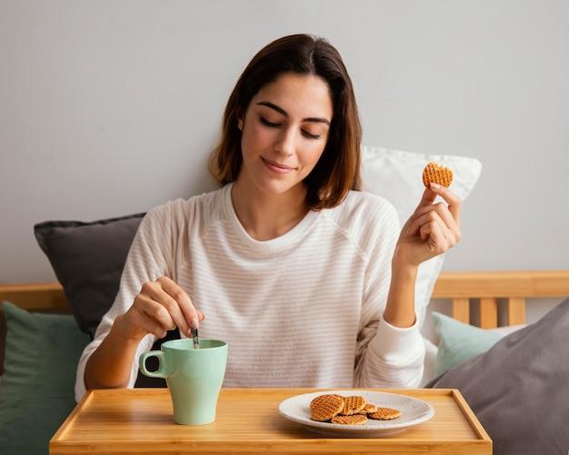 Vista frontal de uma mulher comendo e tomando café em casa