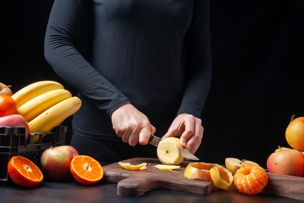 Vista frontal de uma mulher cortando maçã fresca nas frutas da tábua de madeira em uma bandeja de madeira na mesa da cozinha