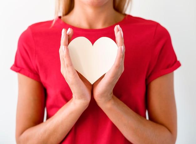 Vista frontal de uma mulher de camiseta segurando um coração de papel