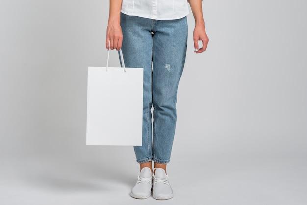 Vista frontal de uma mulher de jeans segurando uma sacola de compras