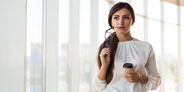 Vista frontal de uma mulher de negócios atraente posando com óculos e café